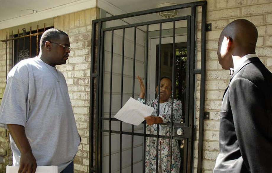 Robert Sampson, left, and Nation of Islam member Nazim Ansari, right, talk with Nadine Wade on Saturday about the killings. The Nation of Islam is also encouraging men to participate in a program that teaches them how to protect the women in the community. Photo: Meenu Bhardwaj, For The Chronicle