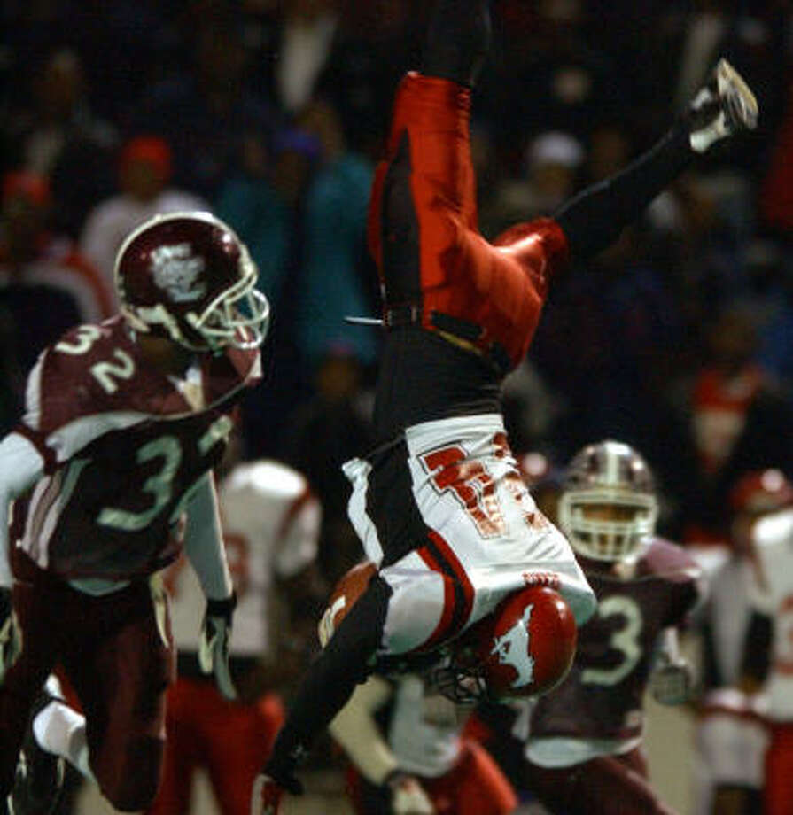 (11/15/02) North shore's #24, Chance Dennis, flips upside down as he dove over Clear Creek's #32, Jackie Rhodes in the first half, during the North Shore High School-Clear Creek football playoffs, Friday evening, at Pasadena Memorial High School Stadium. (Karen Warren/Houston Chronicle)  HOUCHRON CAPTION (11/16/2002):  North Shore's Chance Dennis is headed south after catching a pass and trying to get past Clear Creek's Jackie Rhodes (32) in the first half of Friday night's Class 5A Division I bi-district game at Pasadena Memorial Stadium. North Shore, the state's top-ranked team, advanced with a 41-21 victory. Photo: KAREN WARREN, HOUSTON CHRONICLE