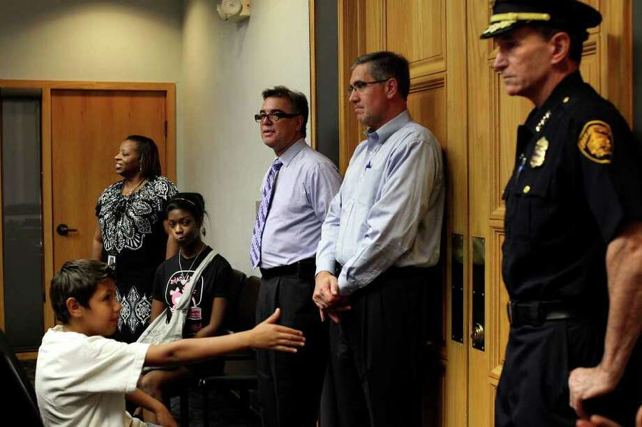 Erik Gonzales, 10, offers his hand to Police Chief William McManus while Deputy City Manager Pat DiGiovanni (center/right) and Cultural Affairs Director Felix Padron take questions from participants, including Abigail Locke, 15. The tour of City Hall on Tuesday, Aug. 9, 2011 was led by Senior Administrative Assistant Denise Luckey (left). Photo: Lisa Krantz/lkrantz@express-news.net / lkrantz@express-news