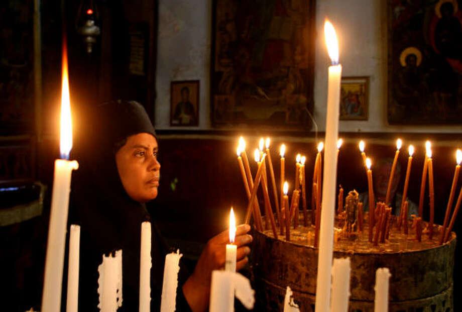 A nun prays at the Church of the Nativity in Bethlehem. Photo: Quique Kierszenbaum, For The Chronicle
