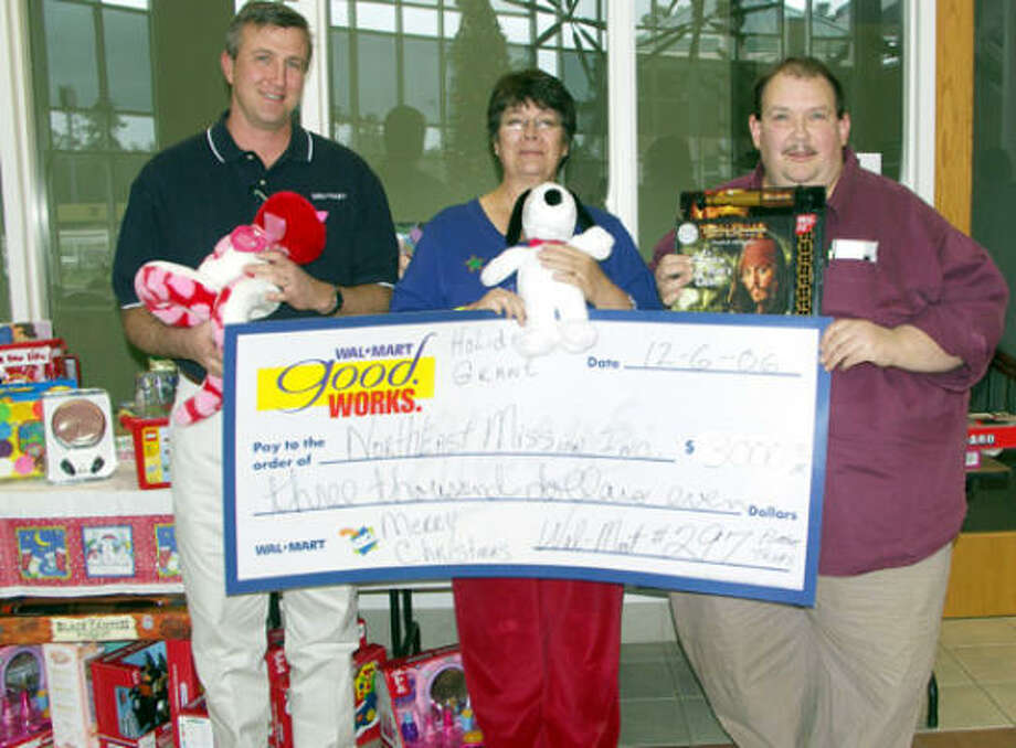 The Mission was the recipient of one of two Wal-Mart employee holiday grants presented by management team members Jeff Randall, left, and Wayne Christian, right,  to Mission executive director Lorie Young. The collected toys were also donated to the Mission for its annual Christmas store on  Dec. 16.  A holiday grant of $1,500 was also awarded to the Montgomery County Sheriff's Department Photo: Suzanne West