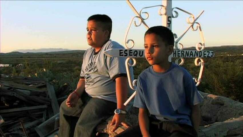Esequiel Hernandez's nephews sit at the well marked with a memorial sign.