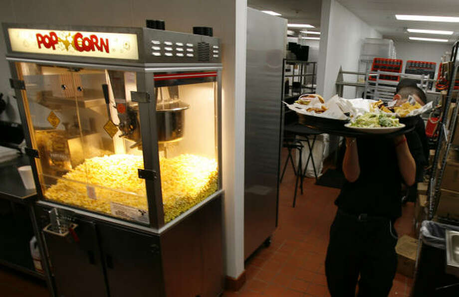 Giving a pass to the traditional popcorn machine, a Movie Tavern server leaves the kitchen with a tray of dinners. Photo: KAREN WARREN, Chronicle