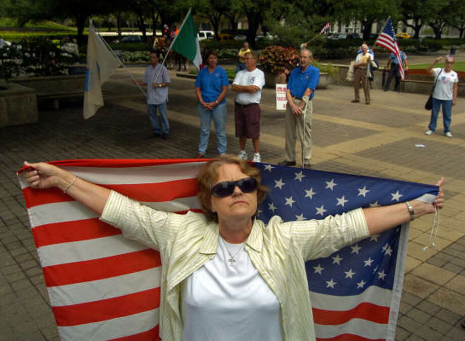 """Brenda Powell, 59, of Houston, who supports tighter border security, spreads out her flag in front of City Hall on Saturday. """"I want to bring awareness that our borders need securing,"""" she said. Photo: Johnny Hanson, For The Chronicle"""