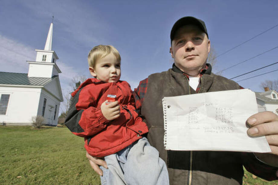 Ben Bangs holds his son, Gavin, and a list of his property taxes for the past six years for his home in Newark, Vt. Bangs wants the state to repeal a statewide property tax, which he says is pushing him and his neighbors to the breaking point. Photo: TOBY TALBOT, AP