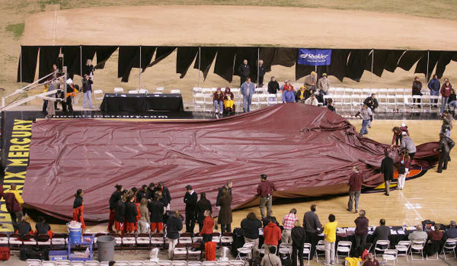 Stadium workers cover the playing court with a tarp as rain begins to fall at Texas Tech's outdoor game with Arizona State. Photo: PAUL CONNORS, AP