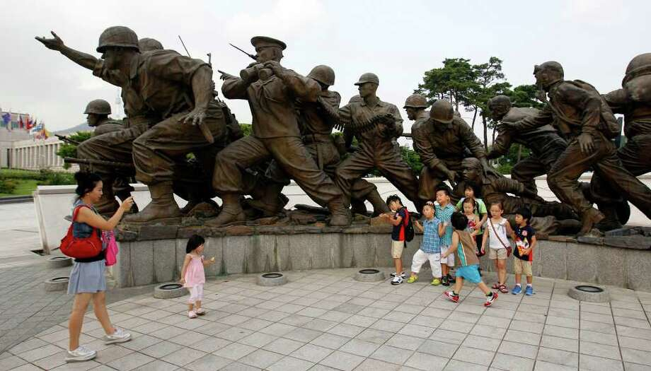 A woman takes pictures of children for souvenir by the monument in remembrance of the Korean War at the Korean War Memorial Museum in Seoul, South Korea, Wednesday, Aug. 10, 2011. South Korean marines returned fire Wednesday after North Korea launched artillery shells into waters near the disputed maritime line that separates the two rivals, South Korean defense officials said. (AP Photo/Lee Jin-man) Photo: Lee Jin-man, STF / AP