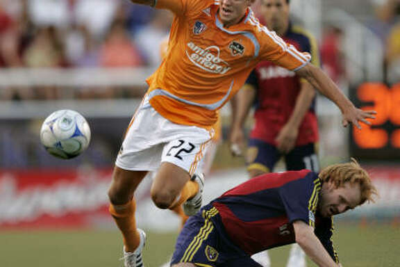 Dynamo midfielder Stuart Holden (22) passes Real Salt Lake midfielder Kenny Cutler during the first half.