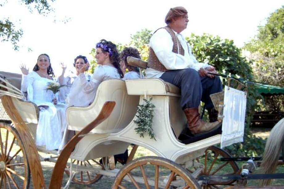 Tracey Leyendecker, left, rides with her bridesmaids in a horse drawn carriage to The Roman Basilica at the Texas Renaissance Festival as she arrives to the beginning of her wedding. Photo: Robert Barreda, For The Chronicle
