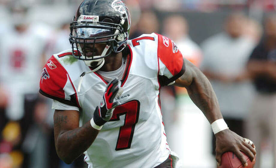 The Cowboys say they must figure out a way to contain Falcons quarterback Michael Vick. Photo: STEVE NESIUS, AP