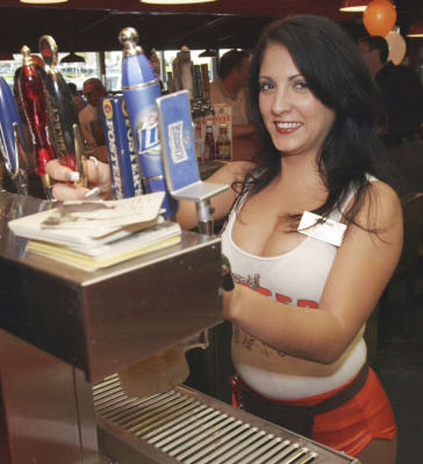 Alexandra Carpanzano, a bartender at a Hooters in Atlanta, shows off the bright smile and skimpy uniform that is the restaurant chain's signature attraction. Photo: Gene Blythe, AP