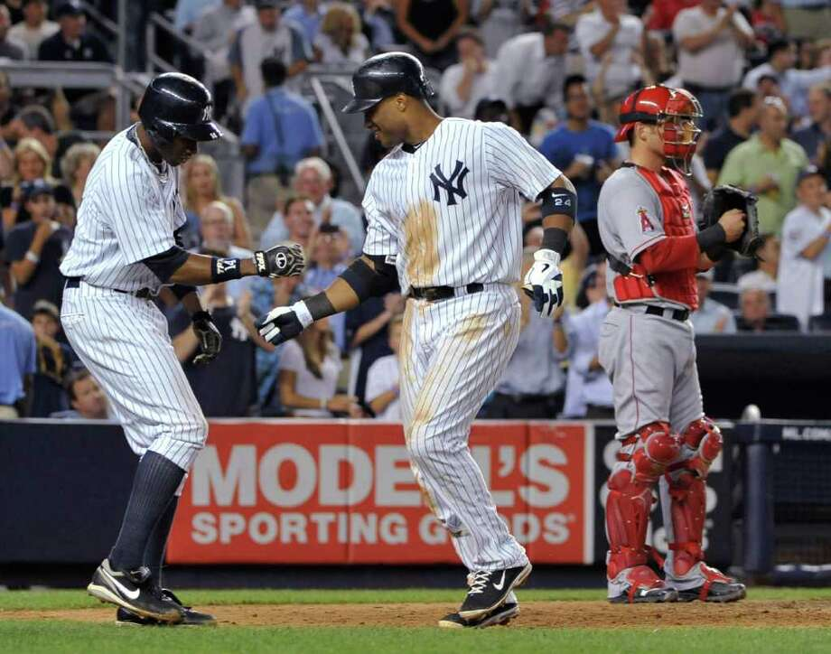 New York Yankees' Curtis Granderson greets Robinson Cano at home plate next to Los Angeles Angels catcher Jeff Mathis after Cano hit a two-run home run that scored Granderson in the seventh inning of a baseball game Wednesday, Aug. 10, 2011 at Yankee Stadium in New York. (AP Photo/Kathy Kmonicek) Photo: Kathy Kmonicek
