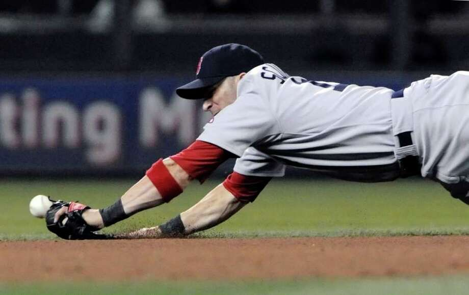 Boston Red Sox shortstop Marco Scutaro makes a dive but can't make it for a ball by Minnesota Twins' Trevor Plouffe in the seventh inning of a baseball game Wednesday, Aug. 10, 2011, in Minneapolis. (AP Photo/Jim Mone) Photo: Jim Mone