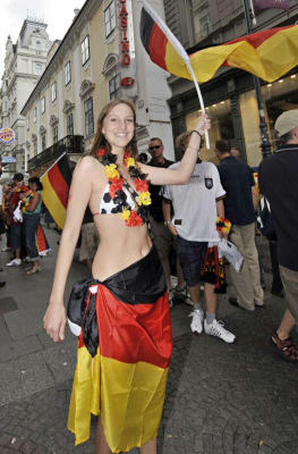 A German fan cheers waving the German flag in downtown Vienna prior to the Euro 2008 European Soccer Championships final between Germany and Spain. Photo: Martin Meissner, AP
