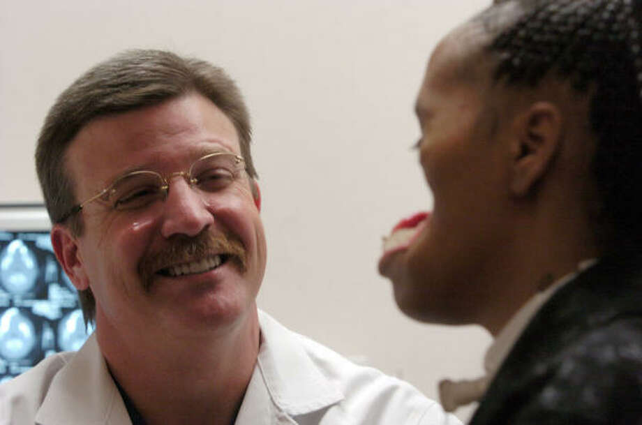Dr. Eugene Alford shares a laugh with Carolyn Thomas as she meets with doctors at The Methodist Hospital on Thursday, Feb. 3, 2005.  Carolyn's  face was destroyed after being shot on Dec. 2003 by her then boyfriend, Terrence Kelly. Photo: Melissa Phillip, Houston Chronicle