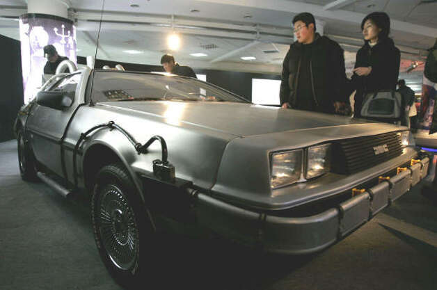 Visitors look at a DeLorean used in the movie Back to the Future at International Classic Cars China Tour. Photo: EUGENE HOSHIKO, Associated Press
