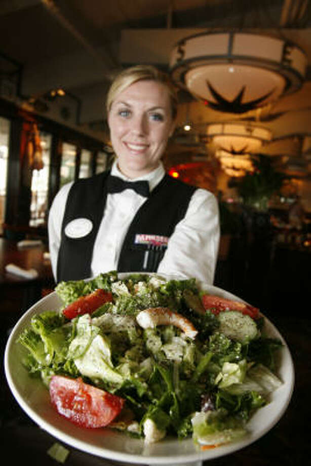 Lisa Lucario gets fresh with customers by preparing a Greek salad tableside at Pappadeaux Seafood Kitchen in Seabrook. Photo: Kevin Fujii, Chronicle