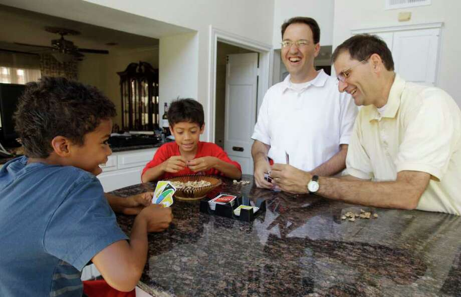 Stephen Milano, center, and Joe Milano, right, with adopted sons, Ruben Milano, 10, left, and Alex Milano, 8, shown Wednesday, Aug. 10, 2011, in Houston are proof that the American family is changing.  Census data shows changing definition of family  with more single parents, more gay parents, etc.  ( Melissa Phillip / Houston Chronicle ) Photo: Melissa Phillip, Staff / © 2011 Houston Chronicle