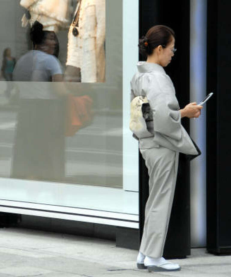 A woman checks her mobile phone in downtown Tokyo recently. Japan got good economic news Friday with the release of healthy industrial expectations. Photo: KATSUMI KASAHARA, AP