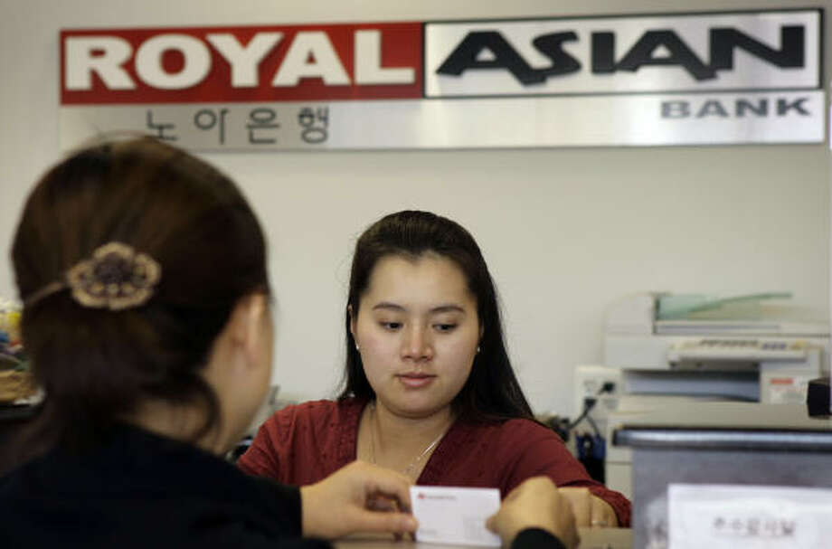 Teller manager Ly Bun processes a customer's transaction at Royal Asian Bank in Upper Darby, Pa. Royal Asian is one of many banks targeting the growing Asian community. Photo: MATT ROURKE, AP