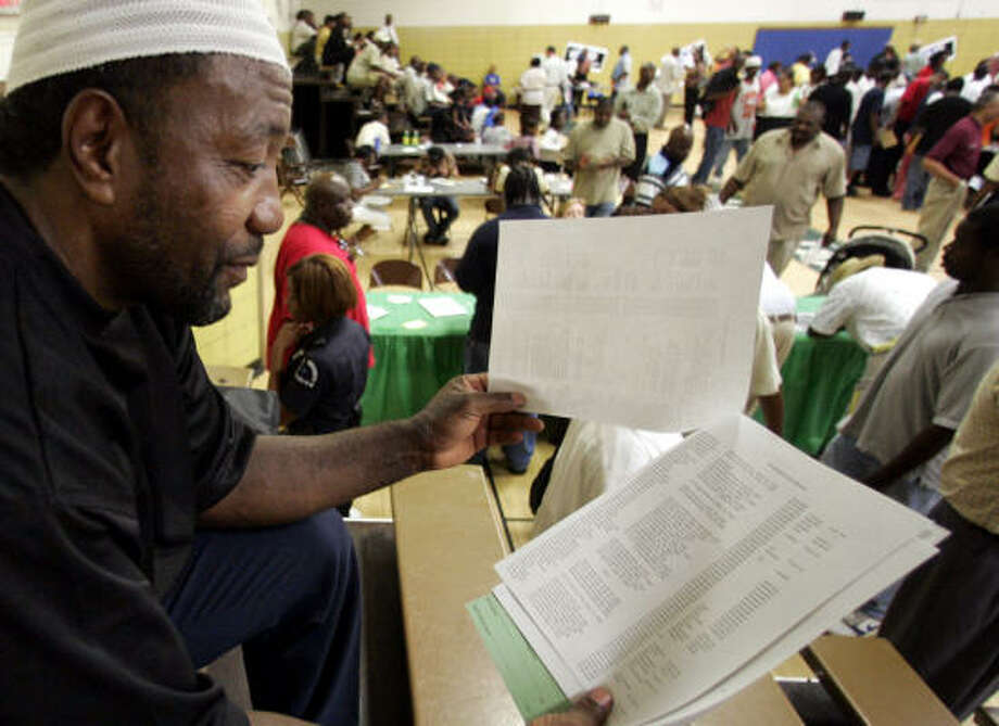 Elton Luckey scans a list of potential employers at a job fair for ex-convicts last week in Dallas. Police said more than 5,000 attended. Photo: DONNA MCWILLIAM, AP