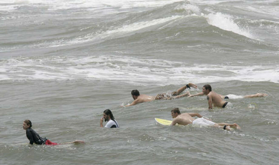 Surfers ride the tide waiting for the perfect wave to arrive at Galveston Beach. Photo: Thomas B. Shea, For The Chronicle