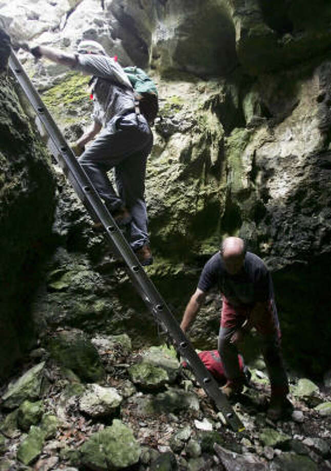 Two visitors to Government Canyon State Natural Area climb down a ladder into a small cave. Photo: WILLIAM LUTHER, SAN ANTONIO EXPRESS-NEWS