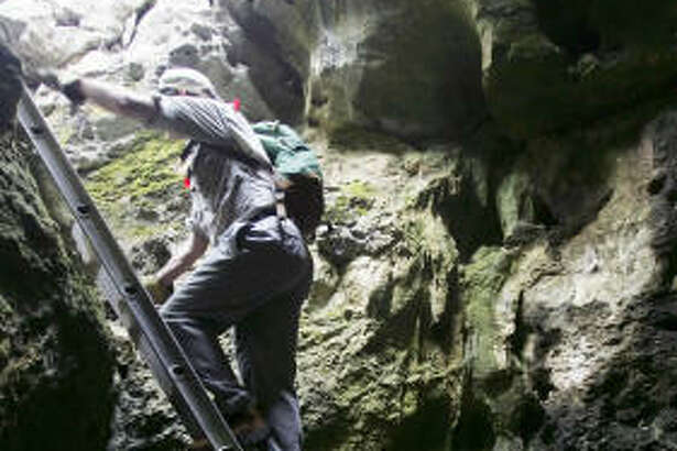 Two visitors to Government Canyon State Natural Area climb down a ladder into a small cave.