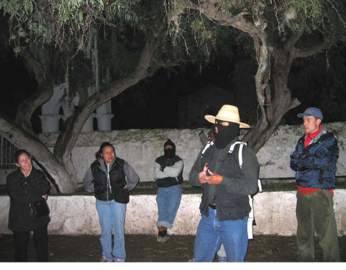 Alfonso Martinez, with hat and ski mask, gives a pep talk before leading visitors on a 4-hour night trek that simulates the experience of crossing the Rio Grande.