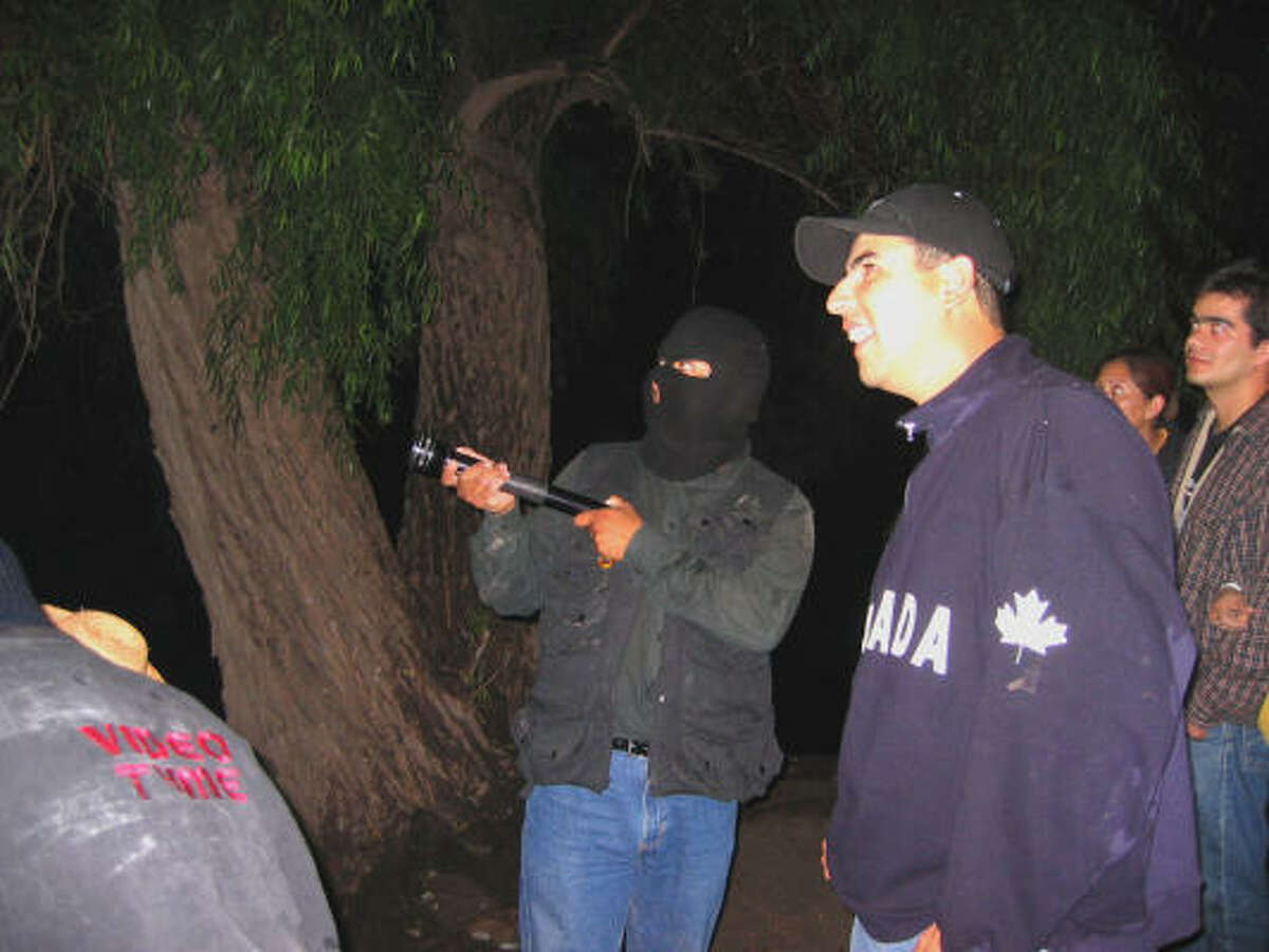 Alfonso Martinez, with ski-mask, points out the route. Martinez, like most residents of the indigenous village of El Alberto, has made several journeys to the U.S. in search of work.