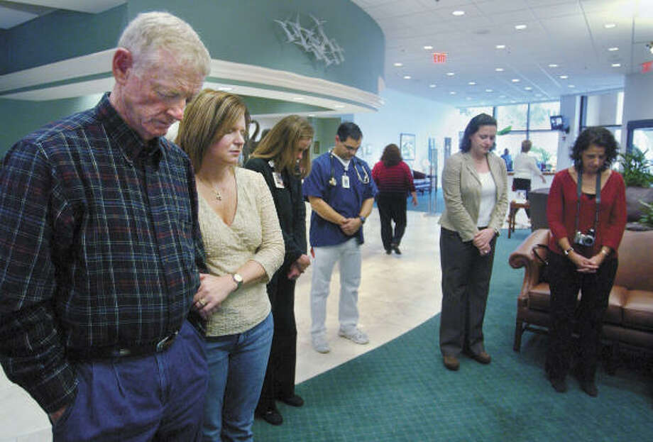 Heart transplant recipient Sonny Graham, left, and his wife, Cheryl, pray during a reunion of organ recipients and donor families Dec. 1 at Hilton Head Regional Medical Center. Photo: JAY KARR, AP