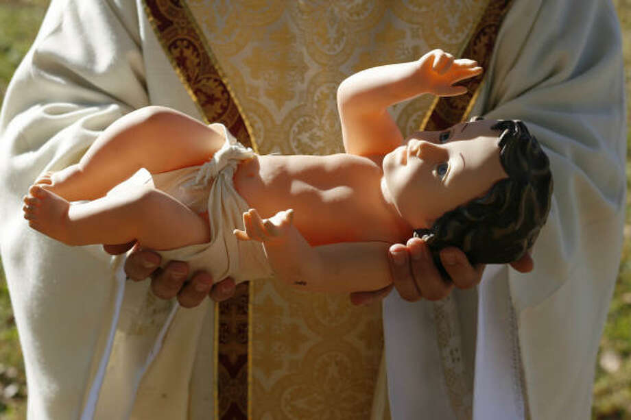 Resting in the hands of pastor Miguel A. Solorzano of St. Philip of Jesus Catholic Church is the infant-Jesus figure whose feet will be kissed by parishioners during the church's Christmas Eve Mass. Photo: Sharon Steinmann, Chronicle