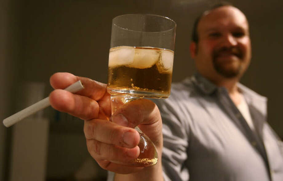 Don Browne shows off a curvy cocktail glass that allows him to hold a cigarette and drink at the same time. Photo: Mayra Beltran, Houston Chronicle