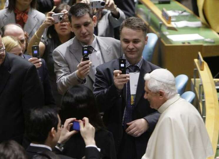 Pope Benedict XVI walks past delegates, most eager to take his picture, inside the United Nations Ge