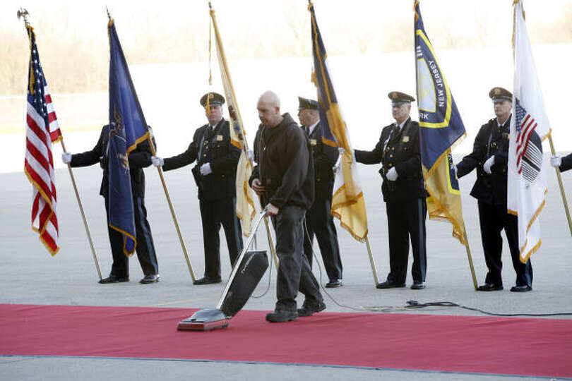 A color guard stand in position as a worker vacuums the red carpet before Pope Benedict XVI arrives