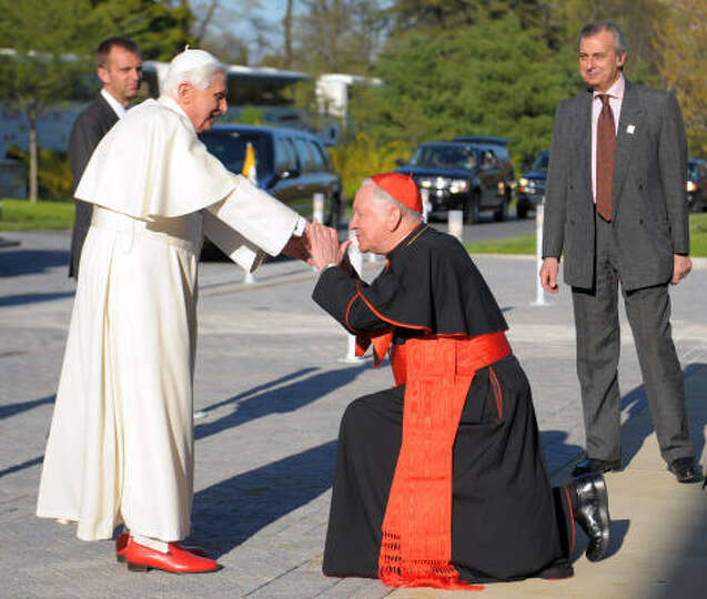 Pope Benedict XVI (L) is greeted by Detroit Cardinal Adam Maida as he arrives to attend a Interrelig