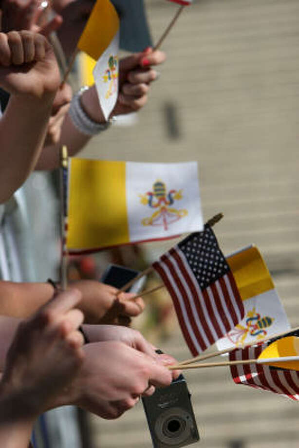 People wave flags before the arrival of  Pope Benedict XVI at the Edward J. Pryzbyla University Center at Catholic University in Washington on Thursday. Photo: NICHOLAS KAMM, AFP/Getty Images