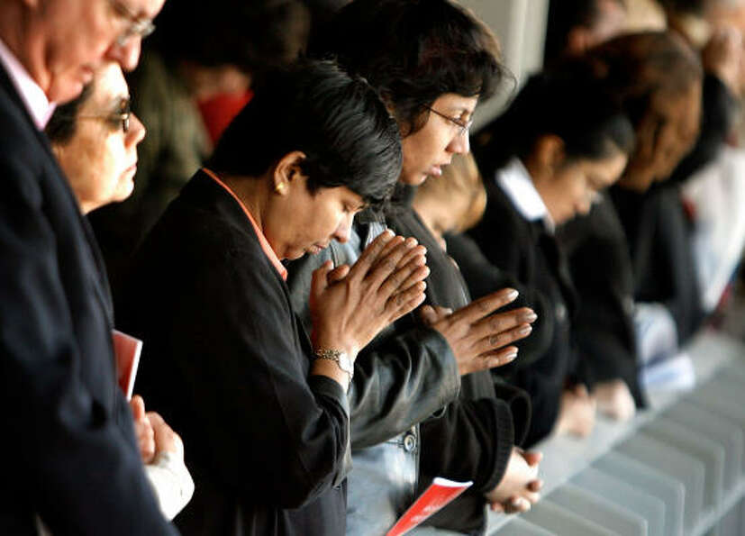 People bow their heads in prayer on Thursday while Pope Benedict XVI celebrates Mass at the new Nati