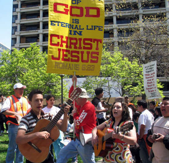 A protestor tries to interrupt a group of musicians and Pope supports along Pennsylvania Avenue in W