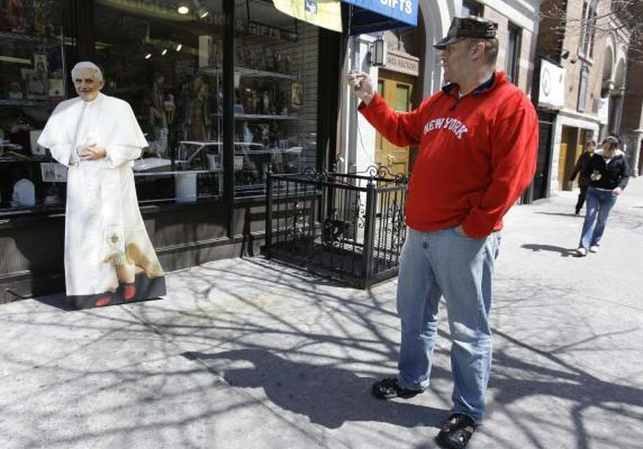 Anthony Delarosa on Wednesday stops to take a picture of a life-size cutout of Pope Benedict XVI displayed outside a Catholic bookstore in the Bronx borough of New York. The pontiff will give Mass at Yankee Stadium on Sunday. Photo: Julie Jacobson, AP