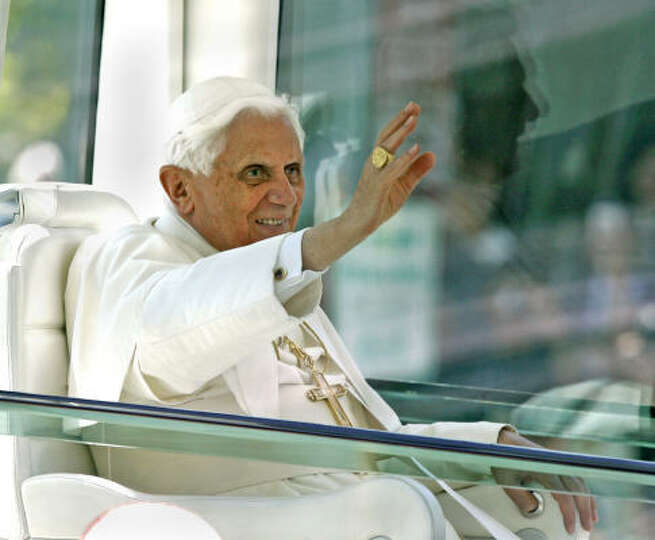 Pope Benedict XVI waves to crowds from the popemobile along Pennsylvania Avenue, just a few blocks f