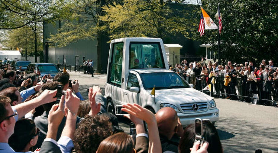 """U.S. Treasury Department employees wave to the """"Popemobile,"""" with Pope Benedict XVI on board, as it leaves the White House on Wednesday. Photo: Chip Somodevilla, Getty Images"""