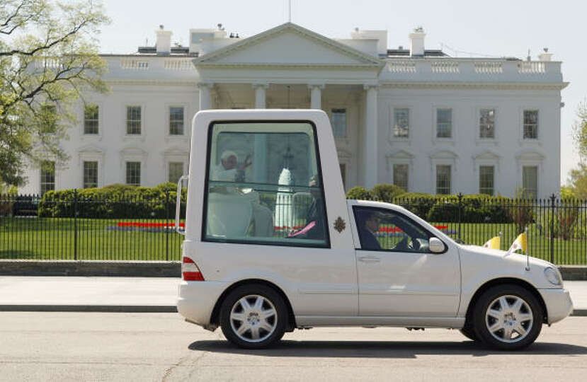 Pope Benedict XVI, riding in the Popemobile, waves while passing the White House in Washington on We
