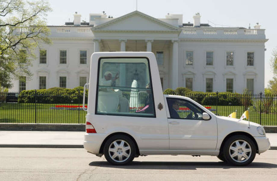 Pope Benedict XVI, riding in the Popemobile, waves while passing the White House in Washington on Wednesdayfollowing an arrival ceremony on the South Lawn. Photo: Gerald Herbert, AP