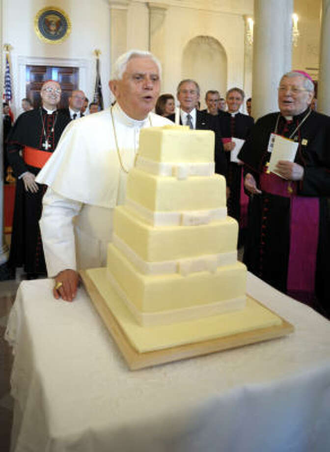 In this photo provided by the Vatican newspaper L'Osservatore Romano, Pope Benedict XVI blows out a candle on a cake to celebrate his 81th birthday during his visit at the White House on Wednesday.  At right are Archbishop Pietro Sambi, Apostolic Nuncio to the United States and President Bush. Photo: AP