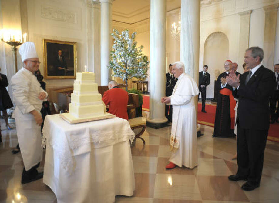 In this photo provided by the Vatican newspaper L'Osservatore Romano, President Bush applauds  as Pope Benedict XVI arrives to blow a candle on a cake to celebrate his 81th birthday during his visit at the White House on Wednesday. Photo: AP