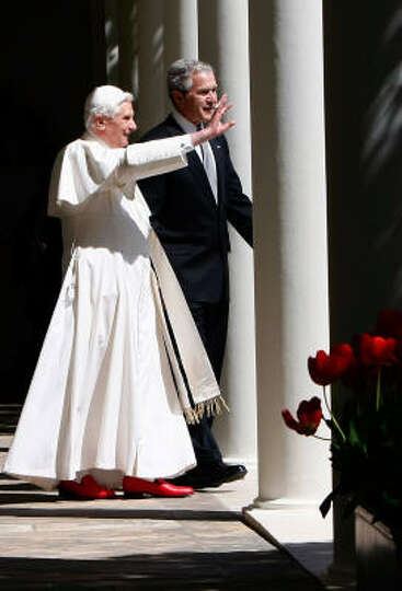 Pope Benedict XVI and U.S. President George W. Bush wave as they walk along the Collonade following