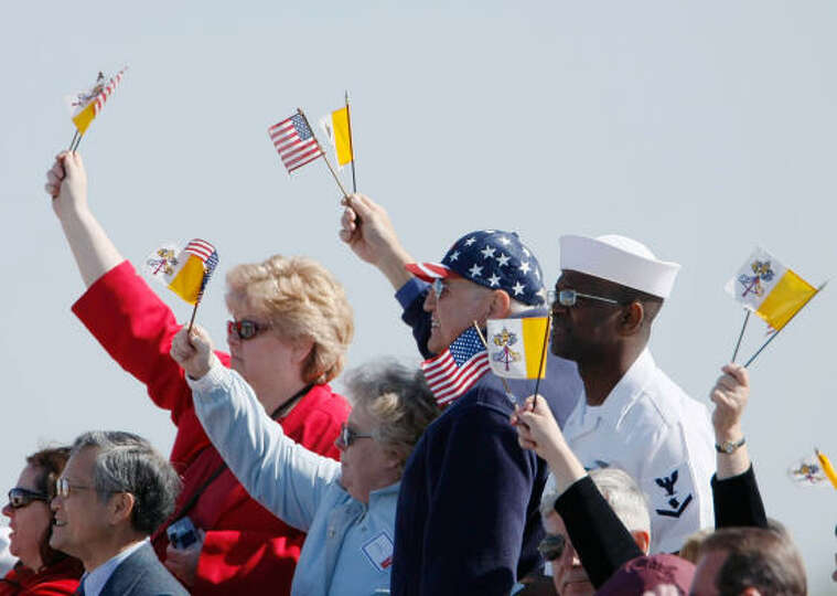 Well-wishers for Pope Benedict XVI wave US and Vatican flags after the plane carrying the Pope arriv