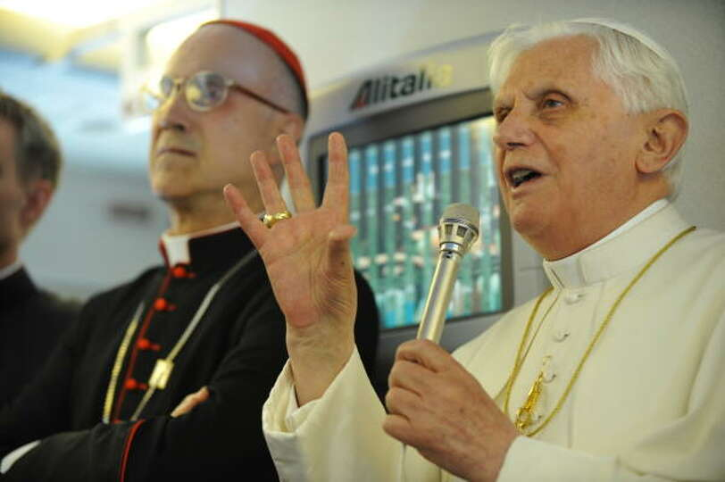 Pope Benedict XVI answers questions from the media beside Cardinal Tarcisio Bertone (L), Vatican Sec