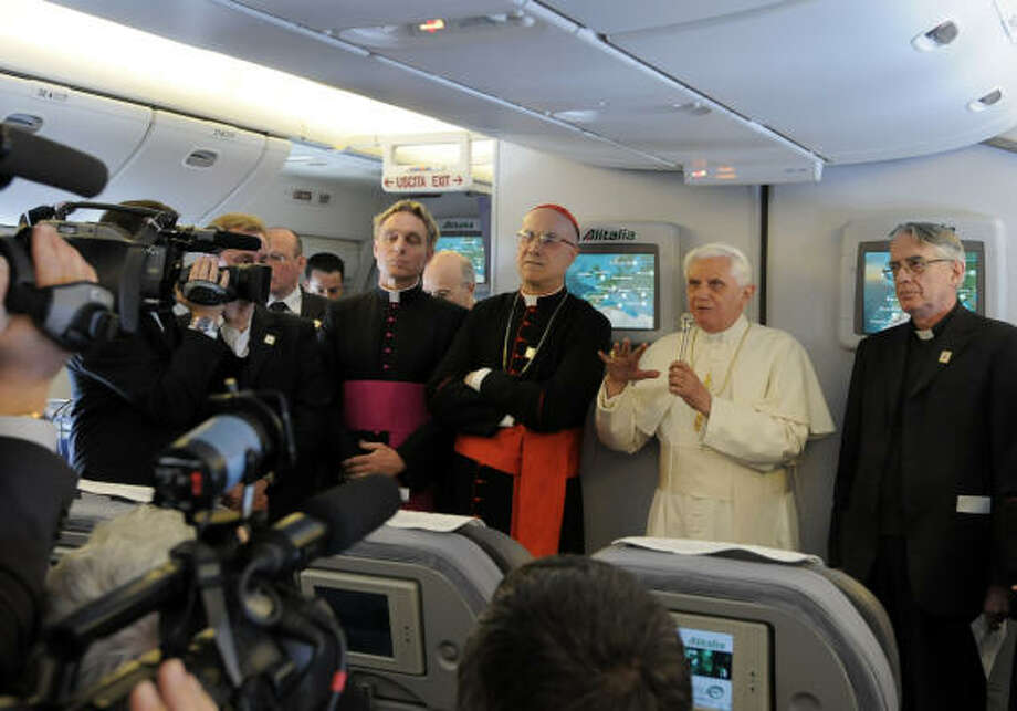 In this photo provided Wednesday by the Vatican newspaper L'Osservatore Romano, Pope Benedict XVI is flanked at right by Father Federico Lombardi, Vatican spokesman, at left by Cardinal Tarcisio Bertone, Vatican Secretary of State, and fourth from right, Rev. Georg Gaenswein, the pontiff's personal aide, as he speaks to the media on board the flight en route to the United States on Tuesday. Photo: AP